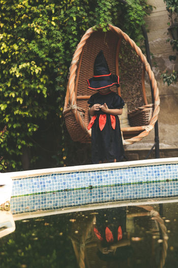 Girl wearing witch costume standing at poolside in back yard