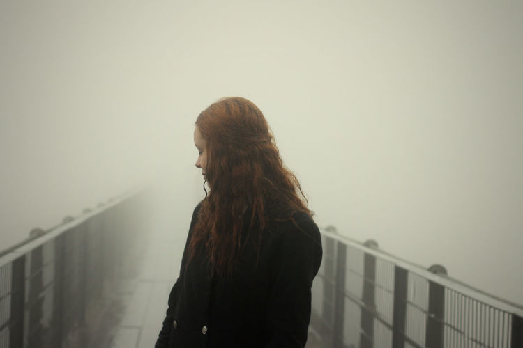 Rear view of a thoughtful teenage girl on footbridge against clear sky