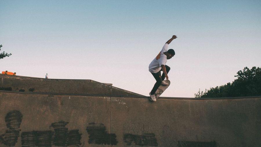 Full length of man skateboarding on sports ramp against clear sky during sunset
