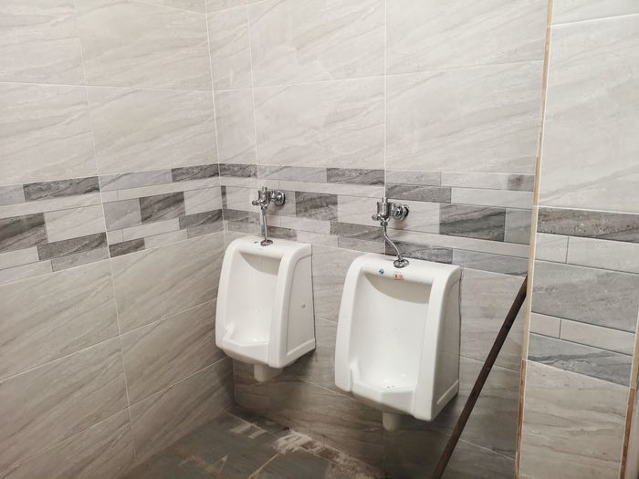 High angle view of urinals against wall in public toilet