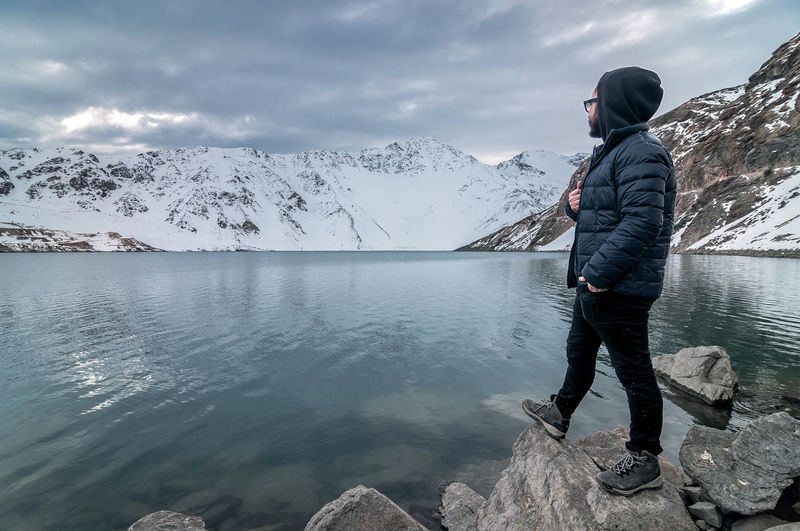 Side View Of Man Standing On Rock By Lake Against Cloudy Sky