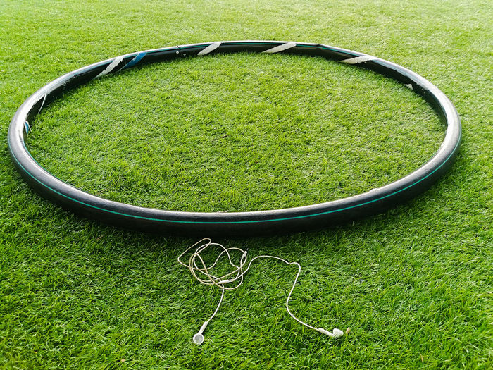High angle view of hula hoop by in-ear headphones on grassy field