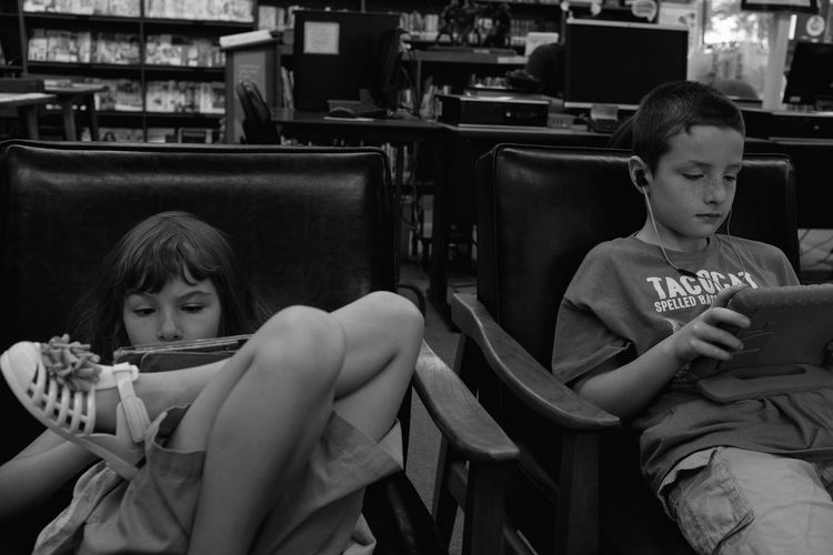 Siblings using digital tablets while sitting on chairs in library