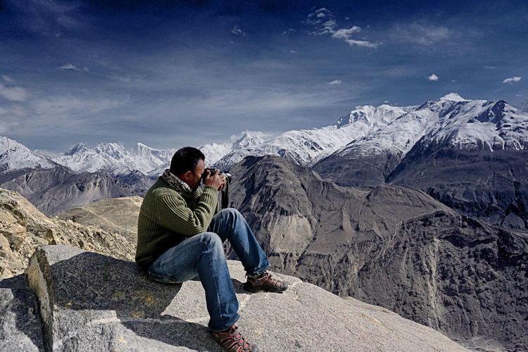 View Of Man Photographing Mountain Range Against Sky