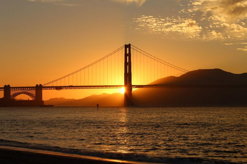 Sunset at Golden Gate bridge Golden Gate Bridge Highway Sunset Bridge - Man Made Structure No Filter Purist No Edit No Filter Pathway Tranquility Travel Destinations Clouds And Sky Reflections In The Water Mountain Cityscape Urban Skyline Sea Skyscraper Horizon Industry Suspension Bridge Bay Of Water Coastal Feature Seascape Coastline