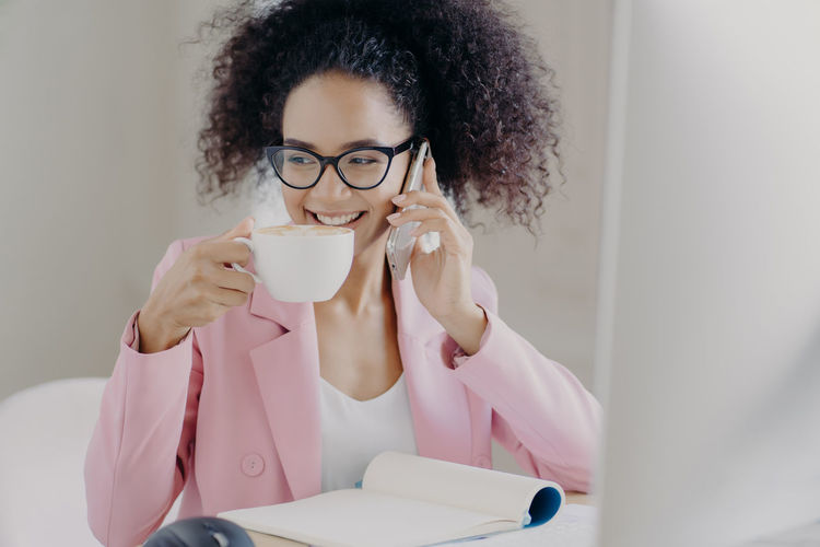 Young woman drinking coffee while talking on phone