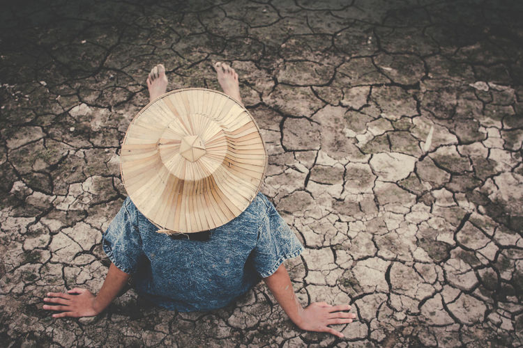 High angle view of girl sitting on drought field