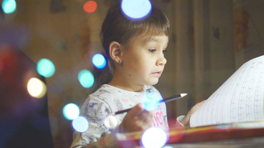Child Childhood Real People Looking One Person Illuminated Headshot Indoors  Portrait Lifestyles Innocence Close-up Casual Clothing Looking Away Focus On Foreground Technology Selective Focus Lens Flare Light Learning Homework