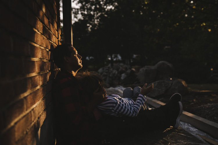 People sitting against wall at night