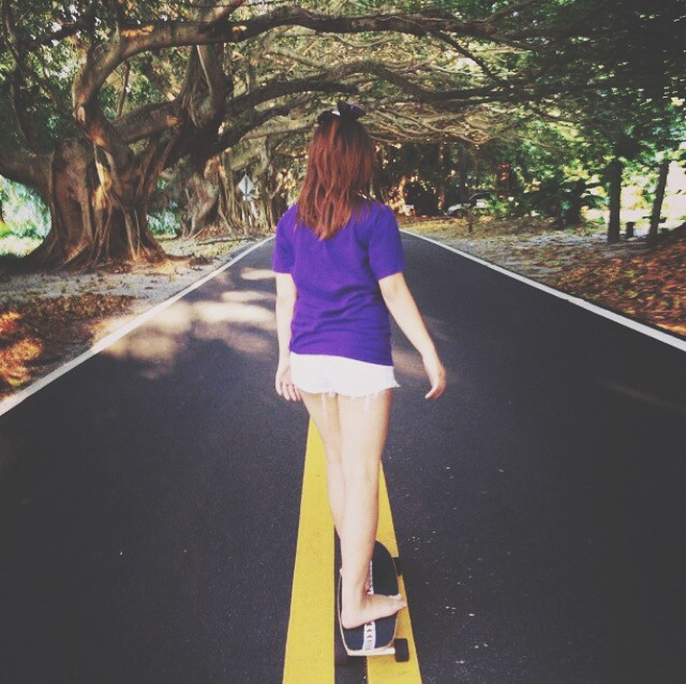 lifestyles, tree, casual clothing, leisure activity, standing, full length, rear view, road, the way forward, person, young adult, long hair, young women, transportation, walking, day, front view, outdoors