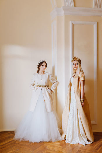 Portrait Of Young Women In Dress Standing Against Wall