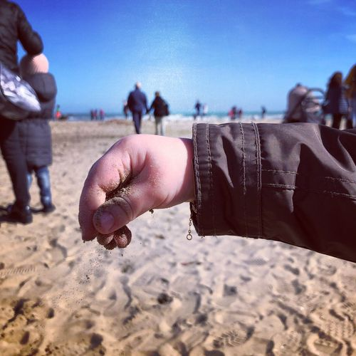 Cropped hand of child at beach