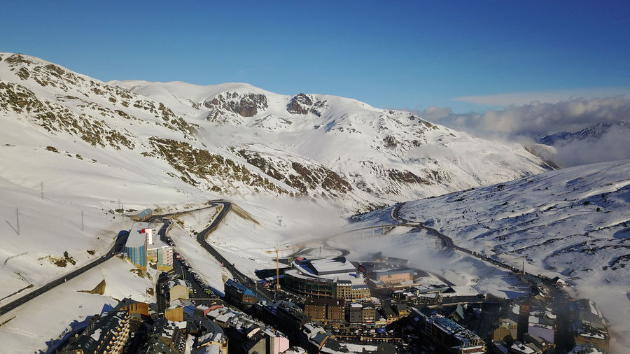 Scenic view of ski resort with snowcapped mountains against clear sky
