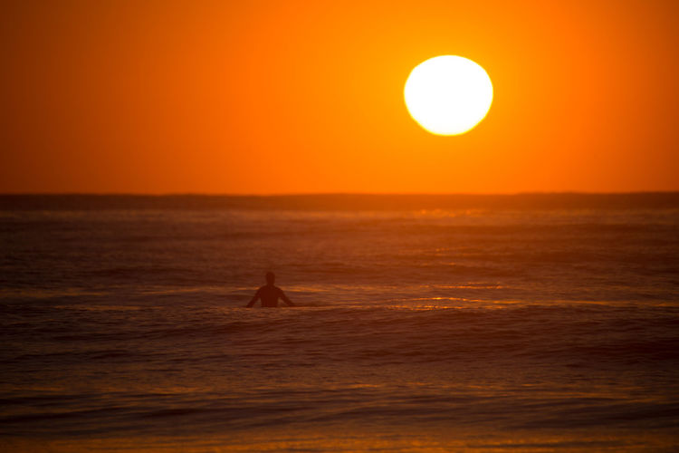 Silhouette surfer surfing in sea against sky during sunset