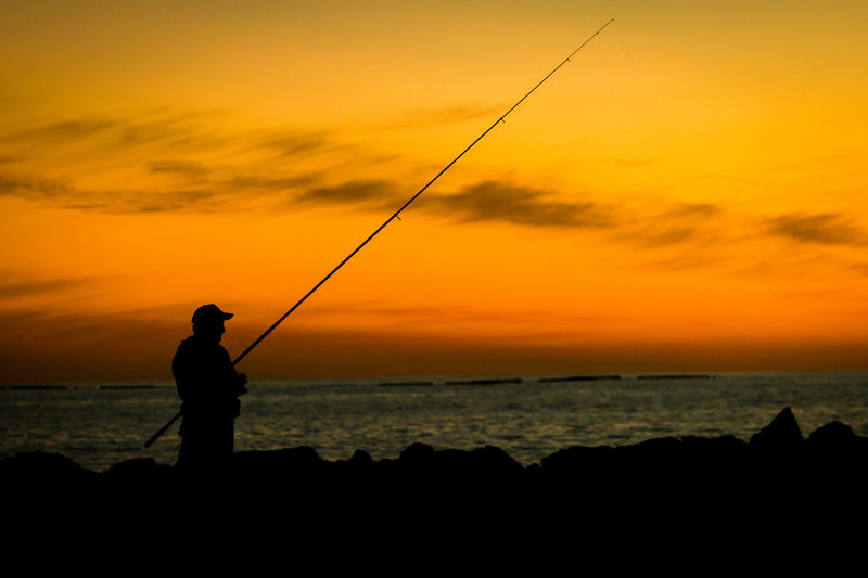 A holiday fisher Silhouette Silhouettes Sunset Silhouettes Sunset_collection Costa Adeje Fishing Fishing Pole Fishing Rod Fishing Tackle Holding Horizon Over Water Leisure Activity Outdoors Real People Sea Silhouette Silhouette_collection Silhoutte Photography Sunset Sunsets Tenerife Teneriffa Tranquil Scene Tranquility Weekend Activities