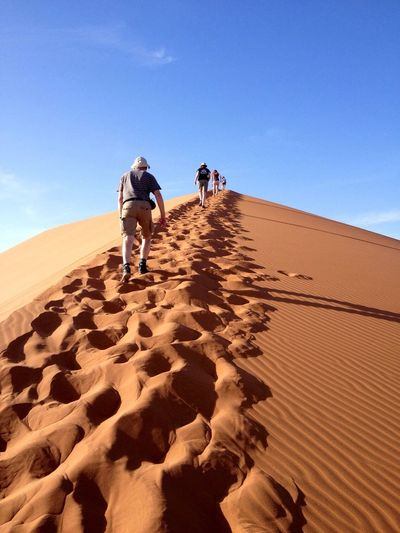 Rear View Of People Walking On Sand At Desert Against Blue Sky