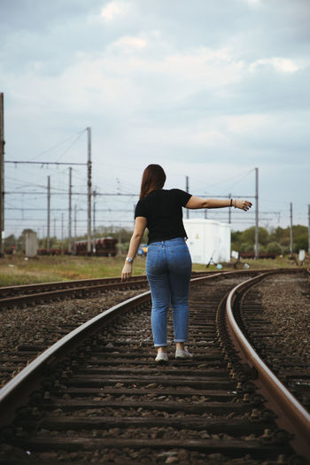 Adult Casual Clothing Cloud - Sky Day Direction Full Length Gravel Hairstyle Inspiration Leisure Activity Lifestyles Mode Of Transportation Nature One Person Outdoors Public Transportation Rail Transportation Railroad Track Real People Rear View Sky Track Transportation Women