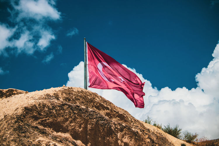 Low angle view of flag on rock against sky