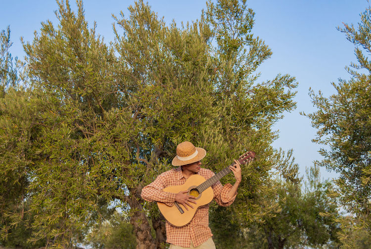 Man playing acoustic guitar while standing against trees