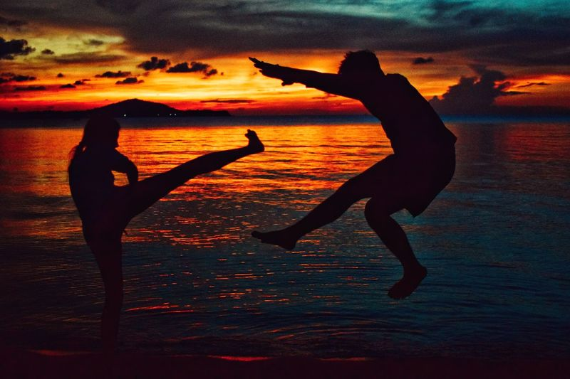 Silhouette of woman kicking man while standing at beach against sky during sunset