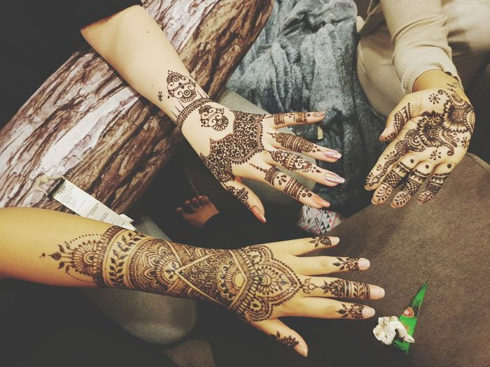 Cropped Image Of Hands Showing Henna Tattoo