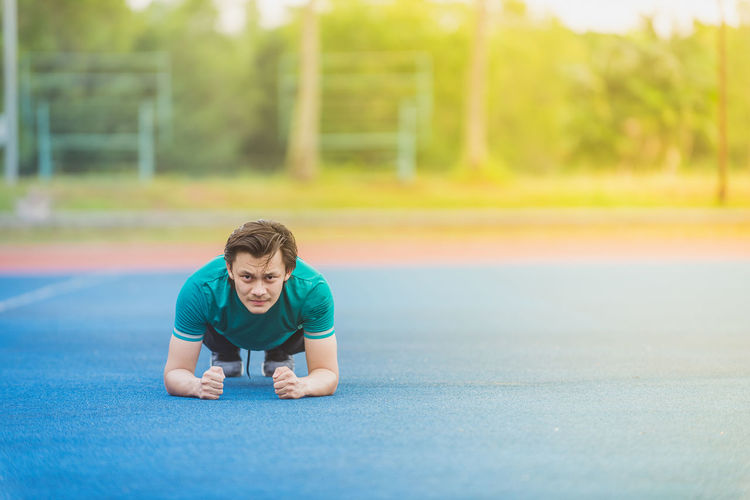 Portrait of young man exercising at stadium