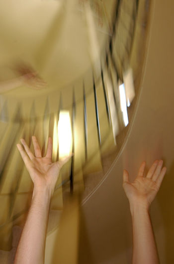 Cropped image of woman with arms raised against stairs