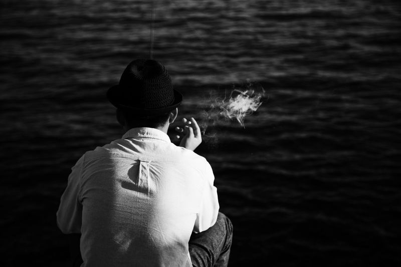 Rear view of man smoking while sitting by sea