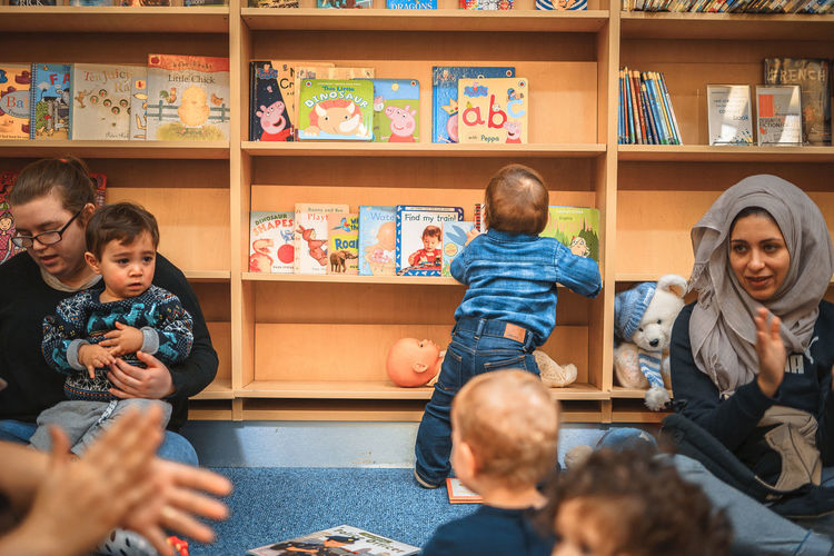 Baby Standing Babyhood Book Bookshelf Boy Boys Classroom Day Education Indoors  Learning Library Real People Shelf Sitting