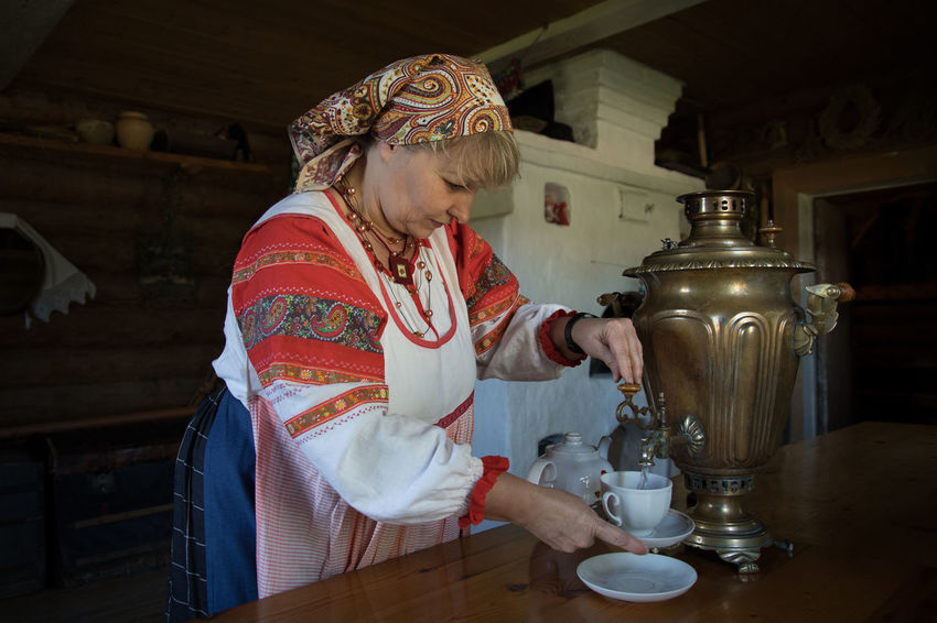 Russia Tradition Traditional Clothing Adult Casual Clothing Drink Females Food Food And Drink Freshness Front View Holding Indoors  Lifestyles One Person Preparation  Real People Refreshment Russian Russian Woman Samovar Table Women Working