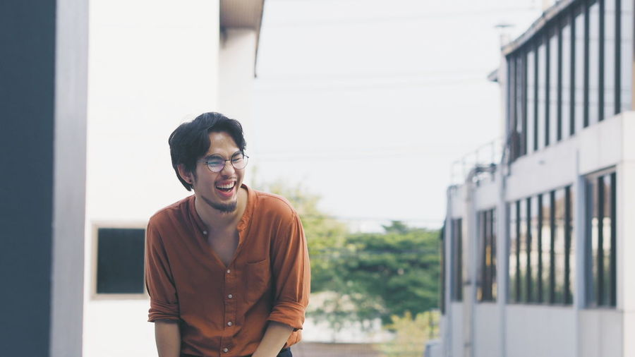 Young Man Laughing While Standing Outdoors
