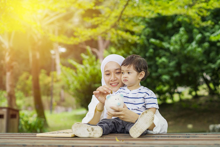 Young woman with her cute son learn how to put coins into piggy bank. Future planning concept. Child Childhood Togetherness Family Males  Men Bonding Son Innocence Boys Offspring Casual Clothing Sitting Emotion Full Length Family With One Child Outdoors Positive Emotion