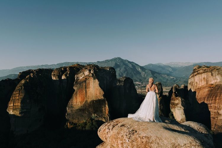 Rear View Of Bride Standing On Rock Against Sky
