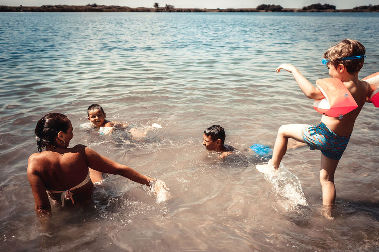 Happy mother and her sons playing in the water during summer day at the beach.