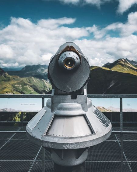 Coin-operated binoculars against cloudy sky