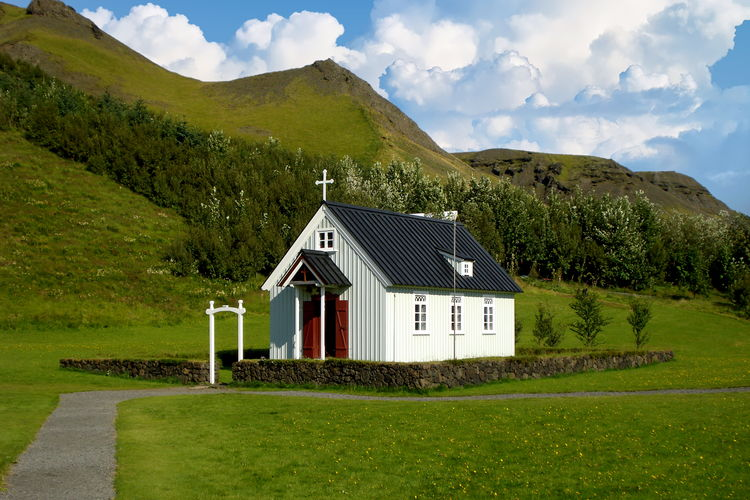 House amidst green landscape and mountains against sky