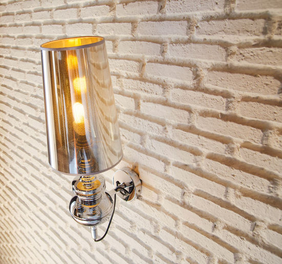 Close-up of illuminated lamp on white brick wall
