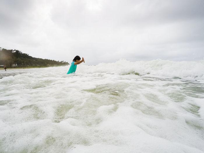 Side view of teenage girl standing in sea against sky