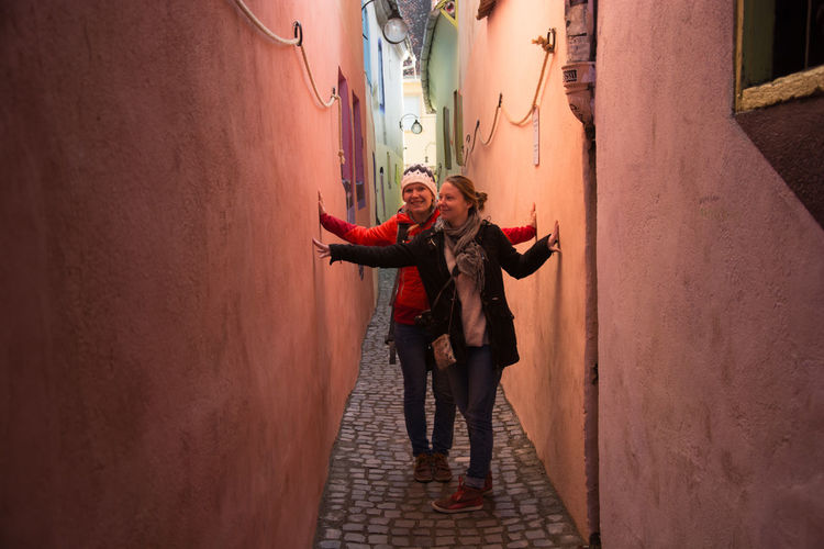 Narrow Narrow Street Strada Sforii Two People Young Women Standing Real People Pink Colourful Houses Travel Photography Traveling Transylvania Rope Street Human Connection Moments Of Happiness