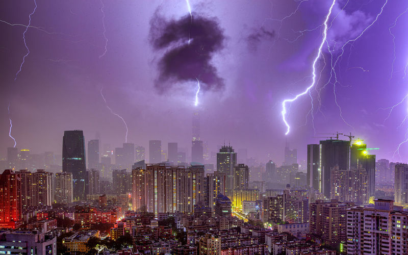 Lightning in sky over city buildings at night