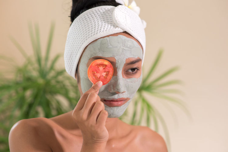 Young woman with facial mask holding tomato slice in spa