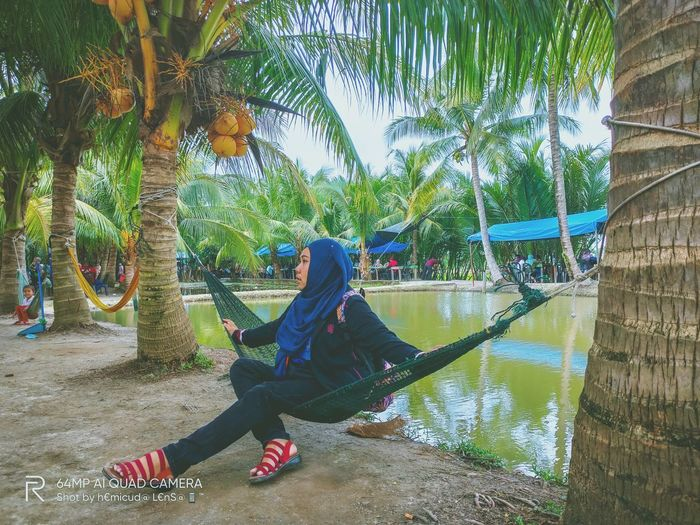 Rear view of woman sitting on palm tree