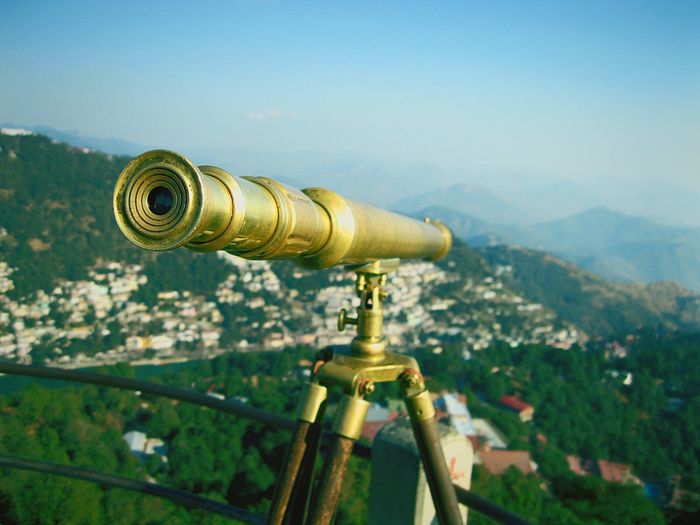 Close-up of old-fashioned metallic binocular over city