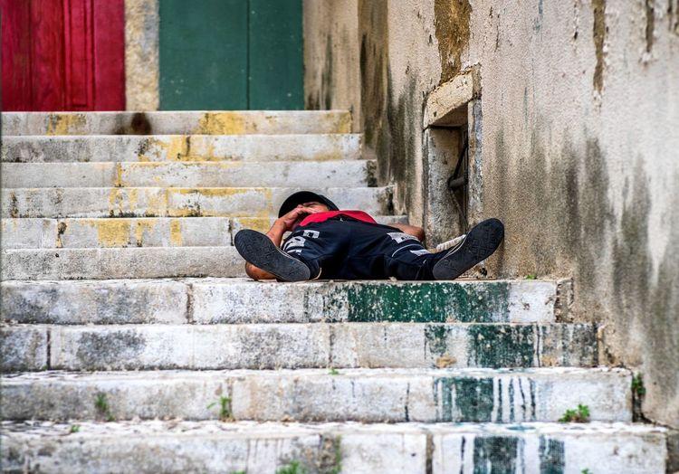 Man sleeping on retaining wall