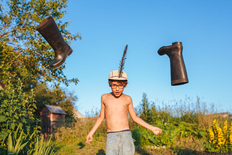 Shirtless boy with flying boots against sky