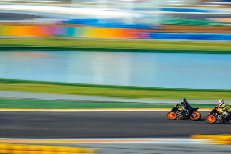 Blurred Motion Of Sportsmen Racing On Motorcycles At Race