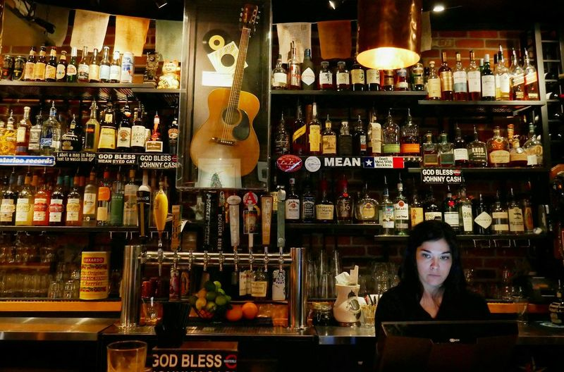 A local bartender. Hanging Out Bartender Bar Restaurant Server Liquor Booze Drinks And Bottles Drinks Local Culture Streetphotography Street Photography Portrait Of A Woman Portrait Working Lumixlounge Candid God Bless Johnny Cash Burgers