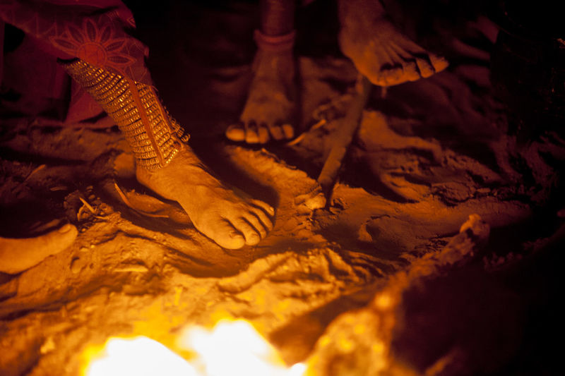 Low section of himba people by bonfire during traditional ceremony at night
