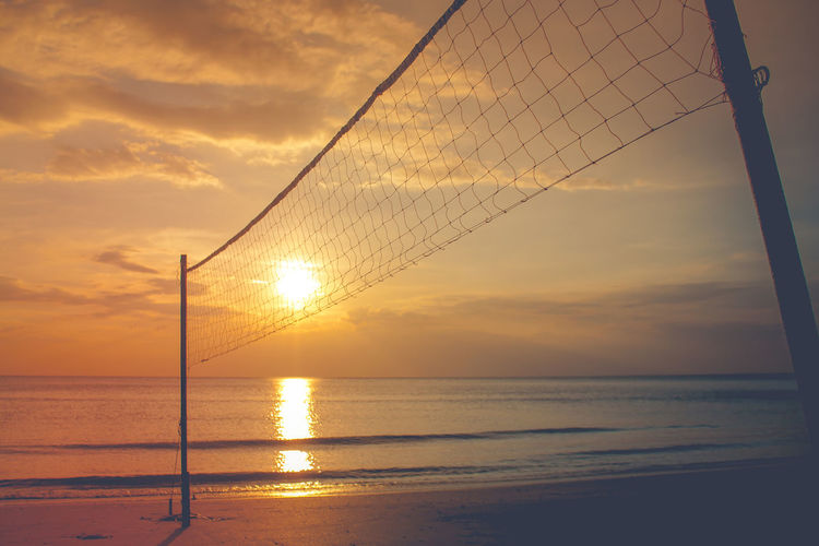 Volleyball net on sand beach with beautiful sunset in twilight time. Abstract Active Activity Background Ball Beach Beautiful Bikini Blue Coast Concept Equipment Exercise Friendship Fun Game Games Hand Happy Healthy Hobby Holiday Jumping Landscape Leisure Lifestyle Net Ocean Outdoor Play Recreation  Relaxation Sand Sea Seaside Shore Silhouette Sky Sport Summer Sun Sunglasses Sunlight Sunshine Team Travel Tropical Vacation Vintage Volleyball