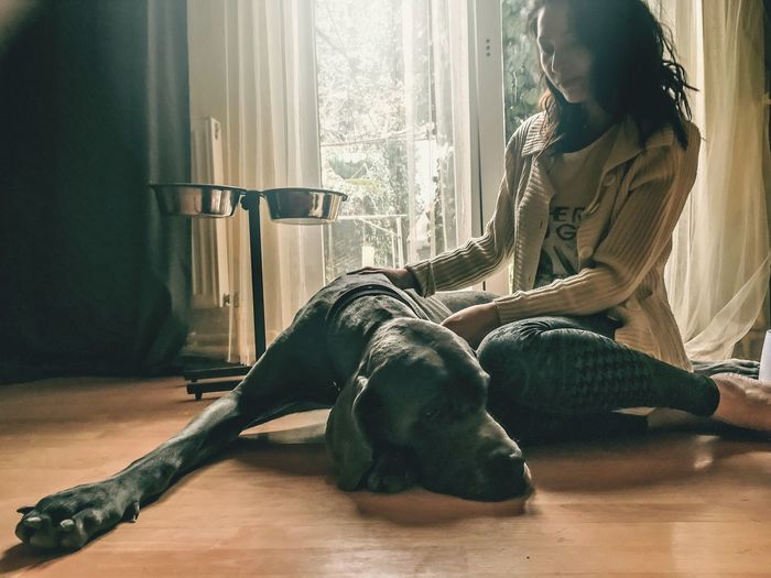 Young woman sitting by dog at home